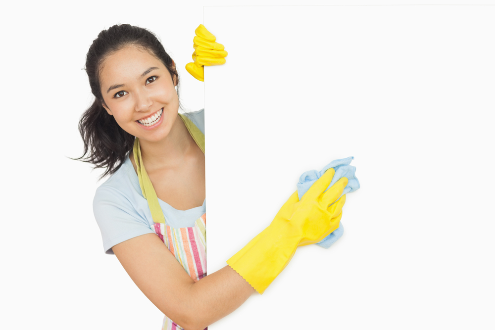 Office cleaning by a Cheerful woman cleaning white surface in apron and rubber gloves