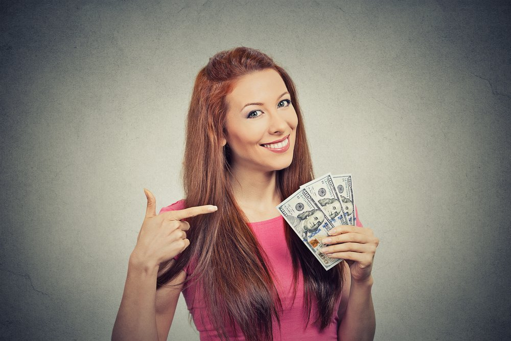 Save money on carpet cleaning Closeup portrait super happy excited successful young business woman holding money dollar bills in hand isolated grey wall background. Positive emotion facial expression feeling. Financial reward