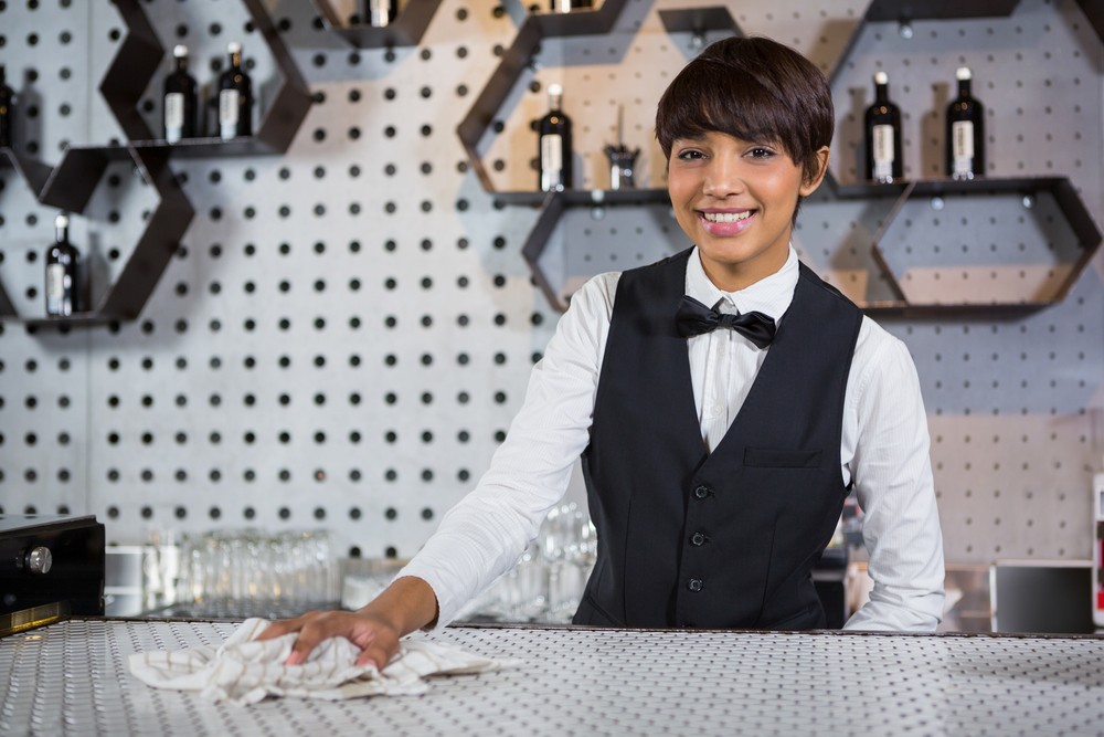 Professional cleaning service with a portrait of smiling waitress cleaning bar counter in bar