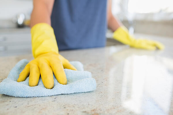 Office cleaning services with a woman cleaning the counter  in the kitchen